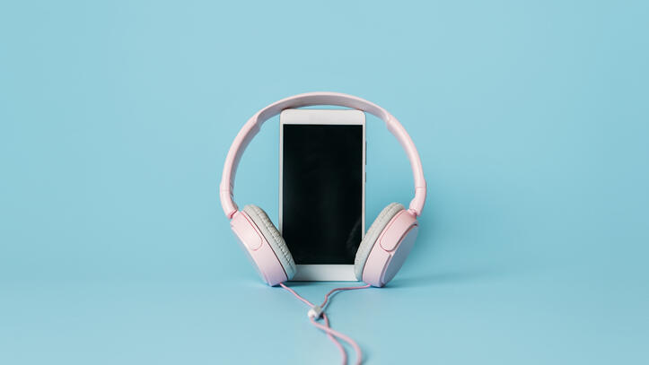 headphones-and-smartphone-on-blue-background-audio-PBSSE85